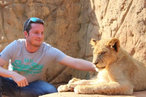 Luis gentlly petting a big kitty in Lion Park